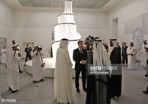 French President Emmanuel Macron speaks with officials as he visits the Louvre Abu Dhabi Museum during its inauguration on November 8 2017 on...