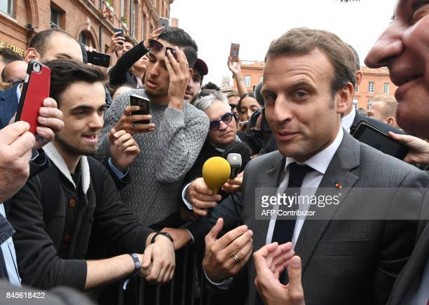 French President Emmanuel Macron speaks with people at the Place du Capitole in Toulouse southern France before attending the round table on 'Housing...