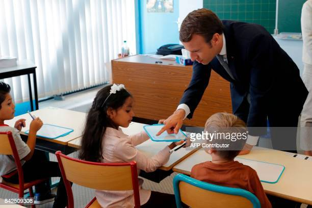TOPSHOT French President Emmanuel Macron speaks with pupils during a visit to a school at the start of the new school year in Forbach eastern France...