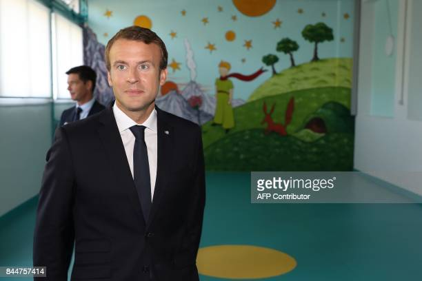 French President Emmanuel Macron stands in front of a mural with an image from 'The Little Prince' as he arrives for a presentation of a 3D model of...
