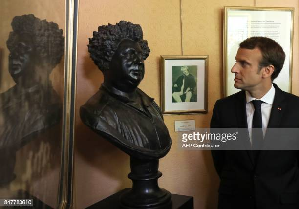 French President Emmanuel Macron stands next to a bust of author Alexandre Dumas during a visit with schoolchildren to The Château de MonteCristo at...