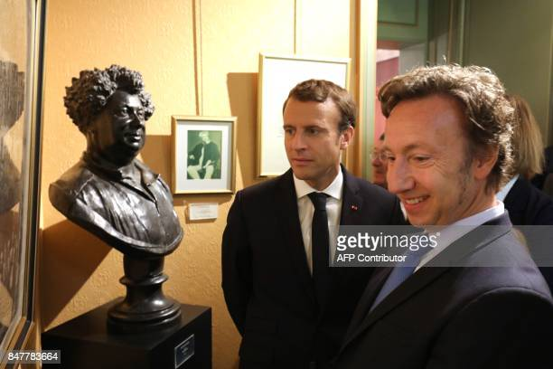 French President Emmanuel Macron stands next to a bust of author Alexandre Dumas as he speaks with television host Stéphane Bern during a visit with...