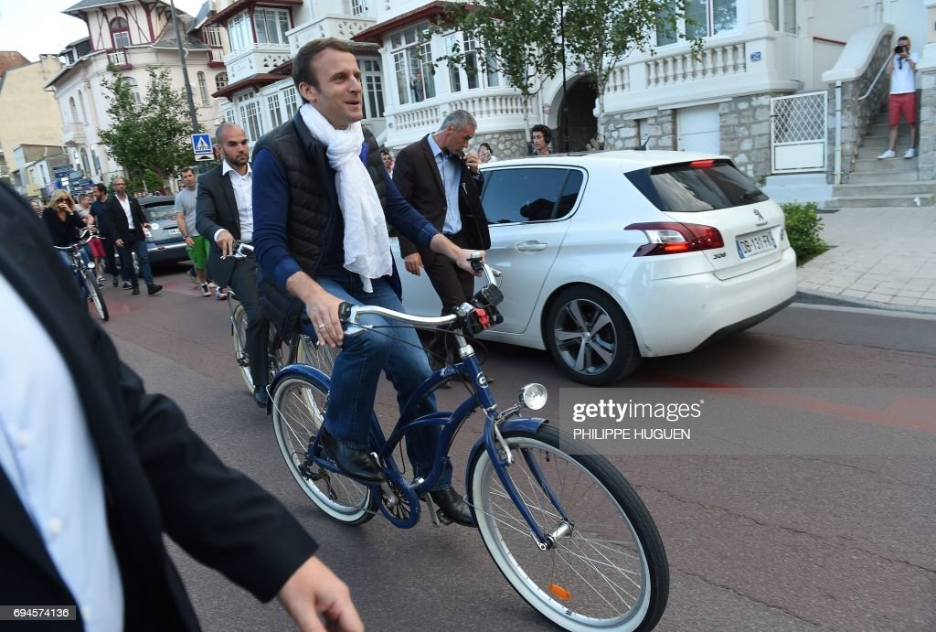 French President Emmanuel Macron (C) takes a bicycle ride on June 10, 2017, in Le Touquet, northern France, the city where Macron votes, on the eve of France's legislative elections. ?French voters go to the polls on June 11, 2017, in the first round of legislative elections with newly elected President Emmanuel Macron seeking to win a strong parliamentary majority. / AFP PHOTO / Philippe HUGUEN