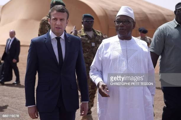 French President Emmanuel Macron talks with Mali's President Ibrahim Boubacar Keita during a visit to the troops of France's Barkhane...