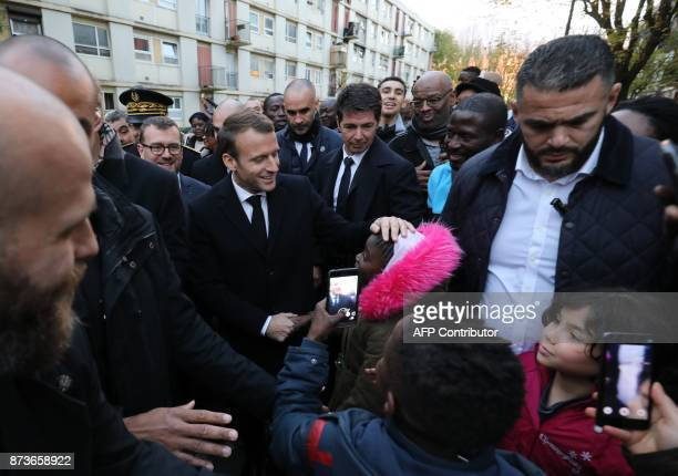 French President Emmanuel Macron touches the head of a child as he meets residents of the Cite du Chene Pointu during his visit focused on the theme...