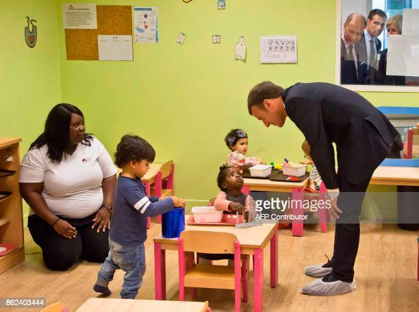 TOPSHOT French President Emmanuel Macron visits a nursery school in Gennevilliers north of Paris on October 17 as part of his action to combat...