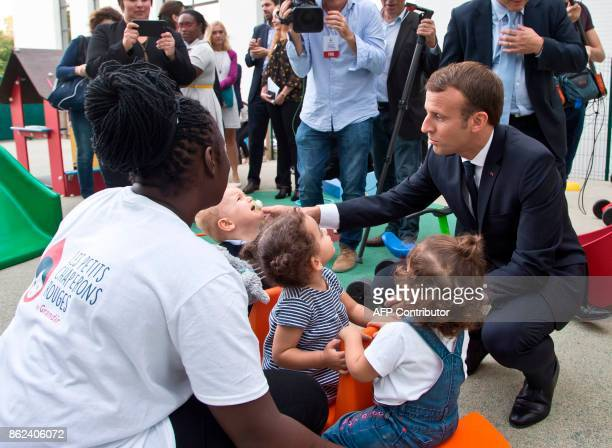 French President Emmanuel Macron visits a nursery school in Gennevilliers north of Paris on October 17 as part of his action to combat children and...