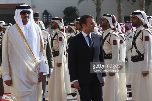 French President Emmanuel Macron walks alongside Qatari Emir Sheikh Tamim bin Hamad alThani during a welcome ceremony in Doha on December 7 2017 /...