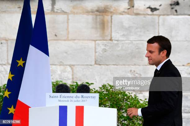 French President Emmanuel Macron walks to the podium to makes a speech following a church service marking the first anniversary of the killing the...