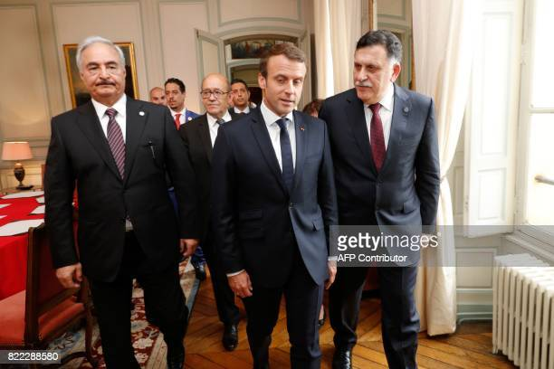 French President Emmanuel Macron walks with French Foreign Affairs Minister JeanYves Le Drian Libyan Prime Minister Fayez alSarraj and General...