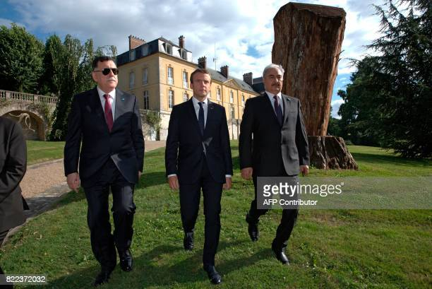 French President Emmanuel Macron walks with Libyan Prime Minister Fayez alSarraj and General Khalifa Haftar commander in the Libyan National Army...