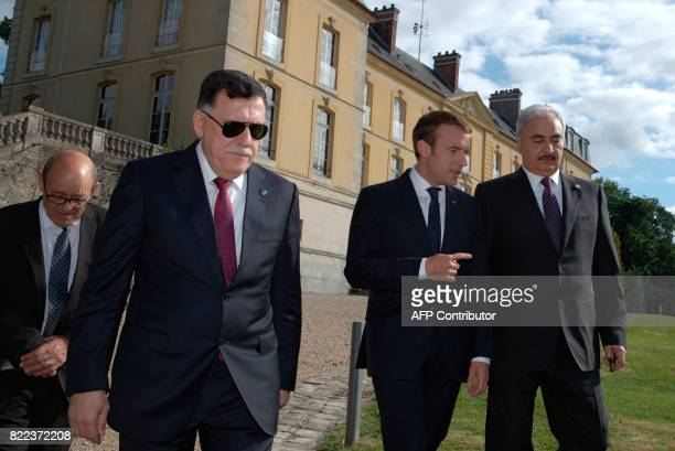 French President Emmanuel Macron walks with Libyan Prime Minister Fayez alSarraj General Khalifa Haftar commander in the Libyan National Army and...
