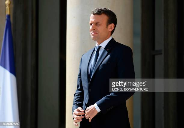 French President Emmanuel Macron watches his Senegalese counterpart leaving following their meeting at the Elysee palace on June 12 2017 in Paris...
