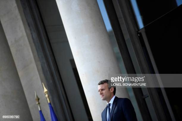 French President Emmanuel Macron watches his Senegalese counterpart as he leaves following their meeting at the Elysee palace on June 12 2017 in...
