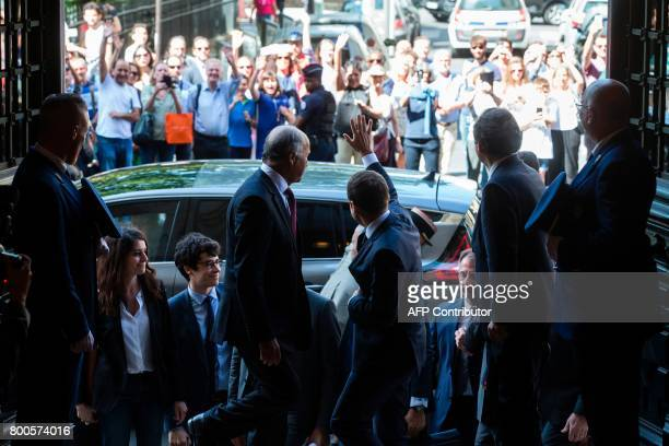 French President Emmanuel Macron waves as former French Foreign Minister Laurent Fabius looks on upon Macron's arrival to attend the World...