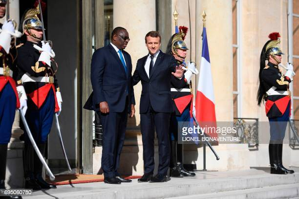 French President Emmanuel Macron waves as he greets his Senegalese counterpart Macky Sall upon his arrival for their meeting at the Elysee palace on...