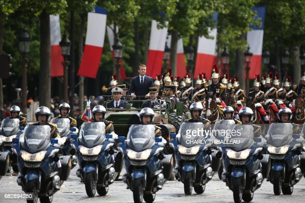 TOPSHOT French President Emmanuel Macron waves as he parades in a car on the Champs Elysees avenue after his formal inauguration ceremony as French...