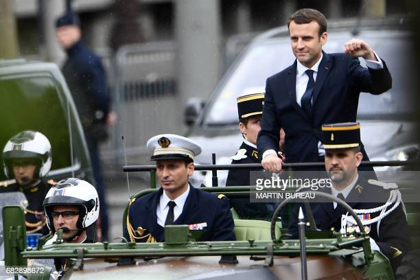 French President Emmanuel Macron waves as he parades in a car on the Champs Elysees avenue after his formal inauguration ceremony as French President...