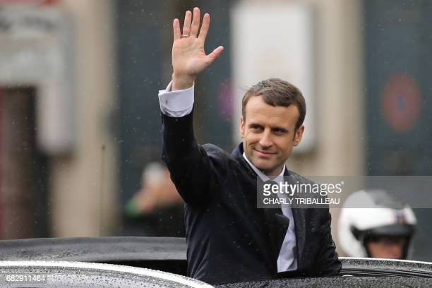 French President Emmanuel Macron waves as he parades in a Citroen DS car on the Champs Elysees avenue after his formal inauguration ceremony as...