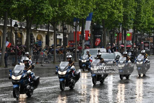 French President Emmanuel Macron waves as he parades under the rain in a Citroen DS car on the Champs Elysees avenue after his formal inauguration...
