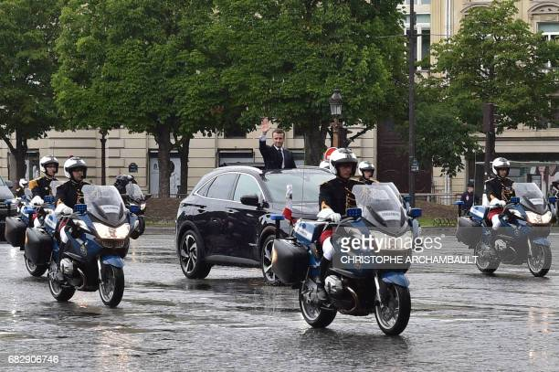 TOPSHOT French President Emmanuel Macron waves as he parades under the rain in a Citroen DS car on the Champs Elysees avenue after his formal...