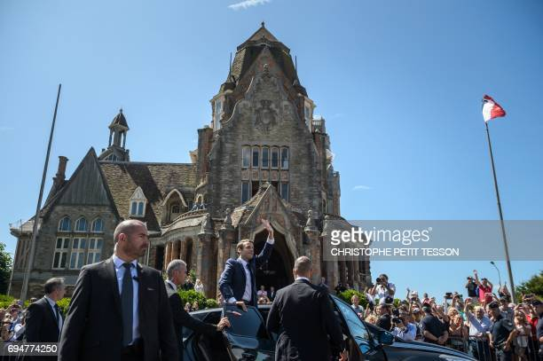 French President Emmanuel Macron waves from his car as he leaves after voting at a polling station during the first round of the French legislative...