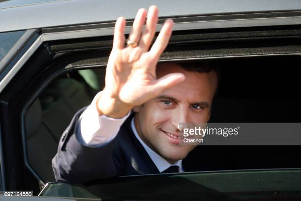 French President Emmanuel Macron waves from his car as he leaves the polling station in the town hall after casting his vote in the second round of...