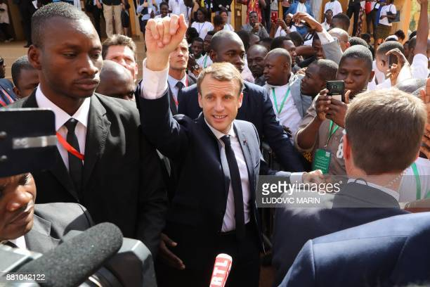 French President Emmanuel Macron waves to residents as he leaves the Ouagadougou University after giving a speech on November 28 in Ouagadougou as...