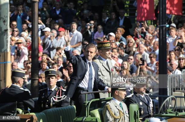 French President Emmanuel Macron waves to the crowds along side Chief of the Defence Staff French Army General Pierre de Villiers as they ride aboard...