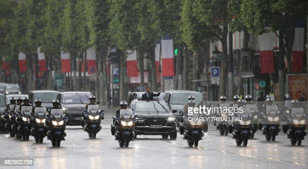French President Emmanuel Macron waves under the rain as he parades in a Citroen DS car on the Champs Elysees avenue after his formal inauguration...