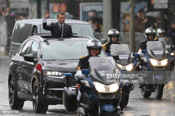 TOPSHOT French President Emmanuel Macron waves under the rain as he parades in a Citroen DS car on the Champs Elysees avenue after his formal...