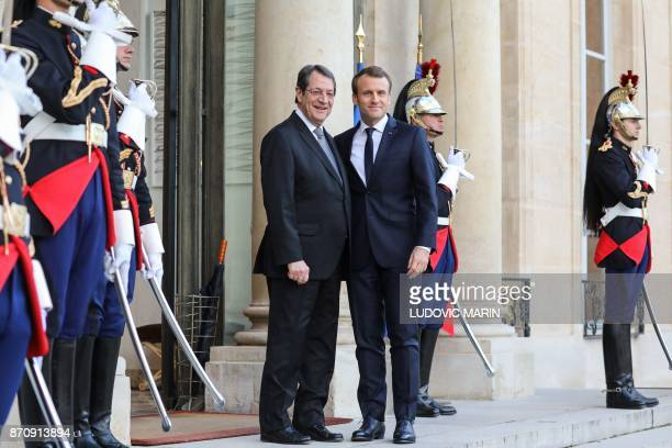 French President Emmanuel Macron welcomes his Cypriot counterpart Nicos Anastasiades upon his arrival for their meeting at the Elysee palace on...