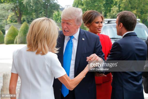 French President Emmanuel Macron welcomes US First Lady Melania Trump while his wife Brigitte Macron welcomes US President Donald Trump outside the...