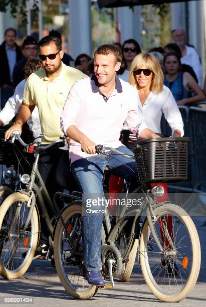 French President Emmanuel Macron and his wife Brigitte Trogneux leave their house on a bicycle on the eve of the second round of the French...