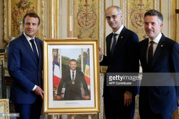 French President Emmanuel poses wit his portrait after receiving a medal by Andorran Prime Minister Antoni Marti and Andorran Parliament President...