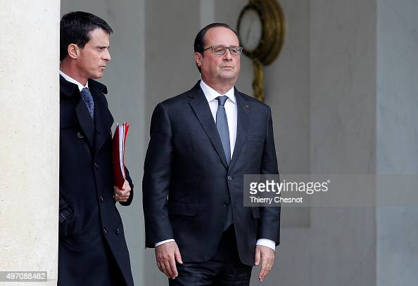 French President Francois Hollande accompanied by France's Prime Minister Manuel Valls gestures while leaving the Elysee Palace in Paris after a...
