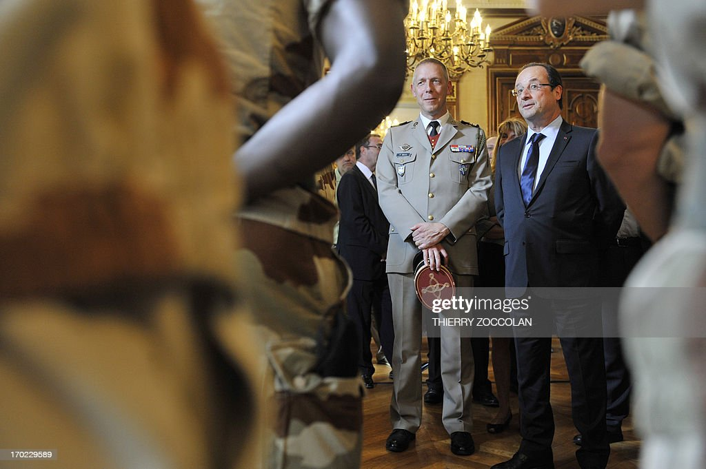 French President Francois Hollande (R), accompanied by lieutenant colonel Patrick Secq, meets with soldiers of the 126th regiment of the Brive-la-Gaillarde infantry, who participated in operation SERVAL in Mali, at the Prefecture in Tulle on June 9, 2013.