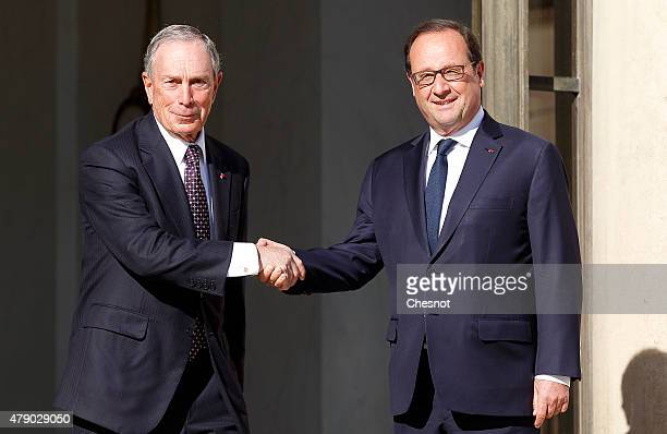 French President Francois Hollande accompanies Former New York city Mayor Michael Bloomberg after their meeting at the Elysee on June 30 in Paris...