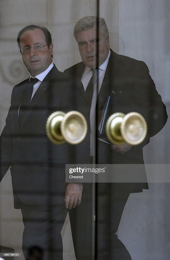 French President Francois Hollande (L) accompanies Junior Minister for Transports and Maritime Economy, Frederic Cuvillier after a weekly cabinet meeting at the Elysee presidential palace on January 29, 2014 in Paris, France.
