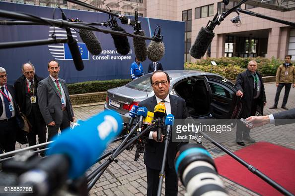 French President Francois Hollande addresses assembled media as he arrives at the Council of the European Union on the first day of a two day summit...