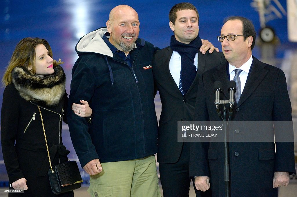 French President Francois Hollande (R) addresses the media as (From L) Diane Lazarevic, her father <a gi-track='captionPersonalityLinkClicked' href=/galleries/search?phrase=Serge+Lazarevic&family=editorial&specificpeople=9859570 ng-click='$event.stopPropagation()'>Serge Lazarevic</a>, France's last remaining hostage, and Clement Verdon, the son of French executed hostage Philippe Verdon, look on after Lazarevic and his daughter landed in a French Republic plane at the Villacoublay military base near Paris on December 10, 2014. Lazarevic, who was snatched by armed men in Mali on November 24, 2011, arrived home on December 10 after three years at the hands of Islamist militants, and was greeted by French President Francois Hollande.
