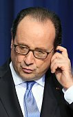 French President Francois Hollande adjusts his ear piece at a joint press conference with Ireland's Prime Minister Enda Kenny at the Goverment...