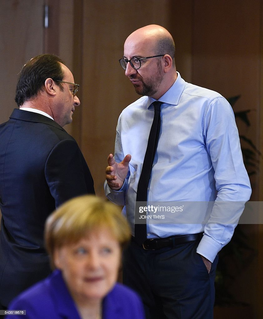 French President Francois Hollande (L) and Belgian Prime minister Charles Michel (R) talk as German chancellor Angela Merkel looks on during the second day of an EU - Summit at the EU headquarters in Brussels on June 29, 2016. European Union leaders will on June 29, 2016 assess the damage from Britain's decision to leave the bloc and try to prevent further disintegration, as they meet for the first time without a British representative. / AFP / JOHN