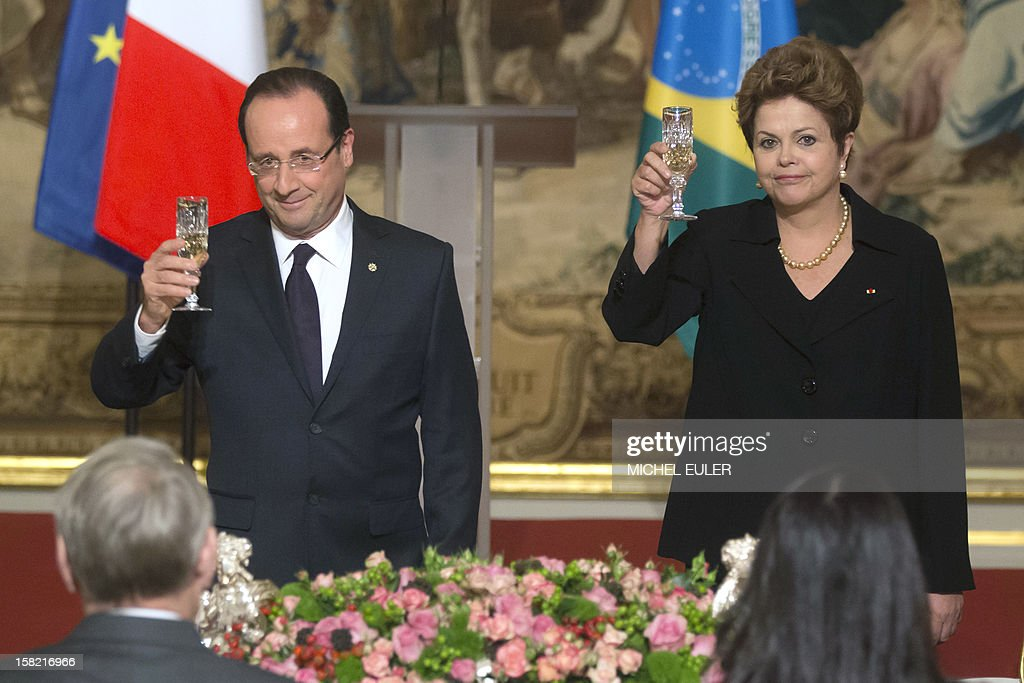 French President Francois Hollande (L) and Brazilian President Dilma Rousseff toast during a state dinner at the Elysee Palace in Paris, on December 11, 2012, as part of Rousseff's two-day visit to France. AFP PHOTO / POOL / MICHEL EULER