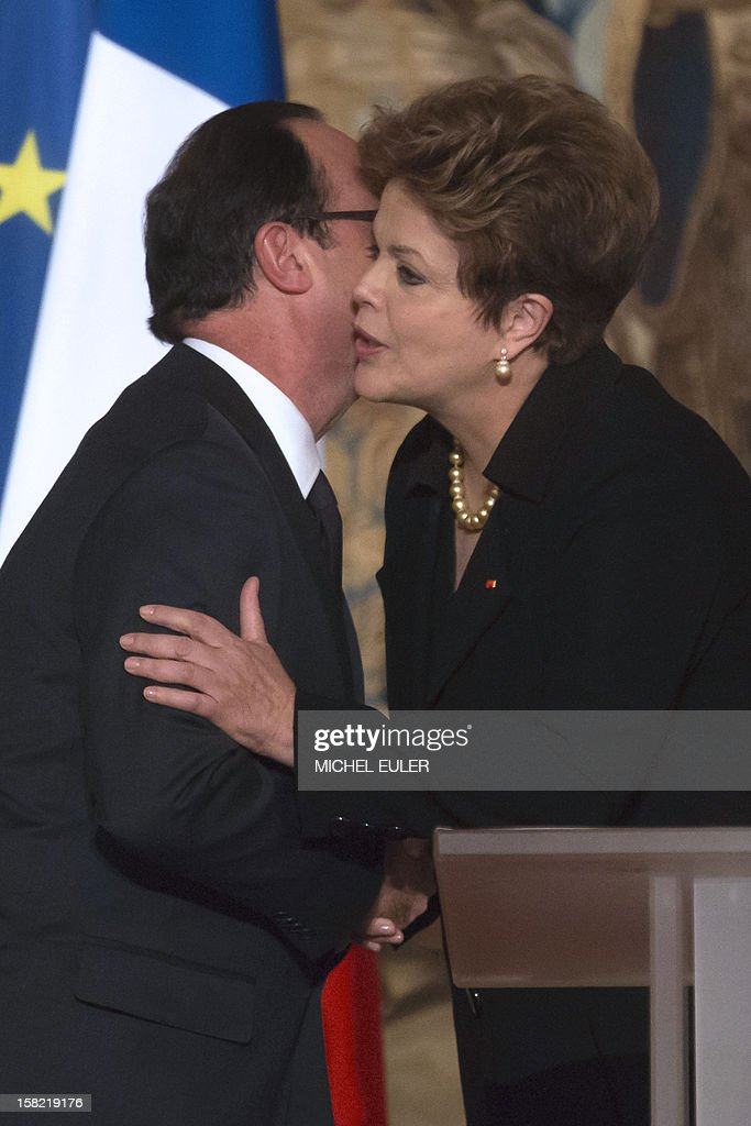 French President Francois Hollande (L) and Brazilian President Dilma Rousseff congratulate each other after their speeches during a state dinner at the Elysee Palace in Paris, on December 11, 2012, as part of Rousseff's two-day visit to France.