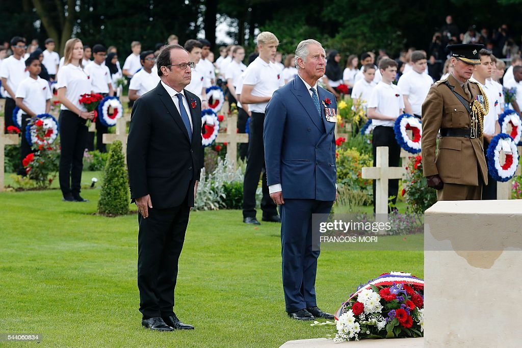 French President Francois Hollande (L) and Britain's Prince Charles (C) stand guard by the Croix du Sacrifice - Cross of the Sacrifice as they attend the memorial ceremony on July 1, 2016 at the Thiepval Memorial, in Thiepval, during which Britain and France will mark the 100 years since soldiers emerged from their trenches to begin one of the bloodiest battles of World War I (WWI) at the River Somme. Under grey skies, unlike the clear sunny day that saw the biggest slaughter in British military history a century ago, the commemoration kicked off at the deep Lochnagar crater, created by the blast of mines placed under German positions two minutes before the attack began at 7:30 am on July 1, 1916. / AFP / POOL / Francois Mori