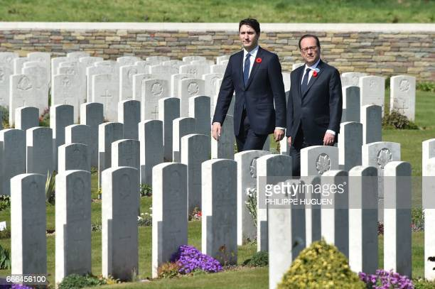 TOPSHOT French President Francois Hollande and Canadian Prime Minister Justin Trudeau walk in the Canadian WWI military cemetery in Vimy near Arras...