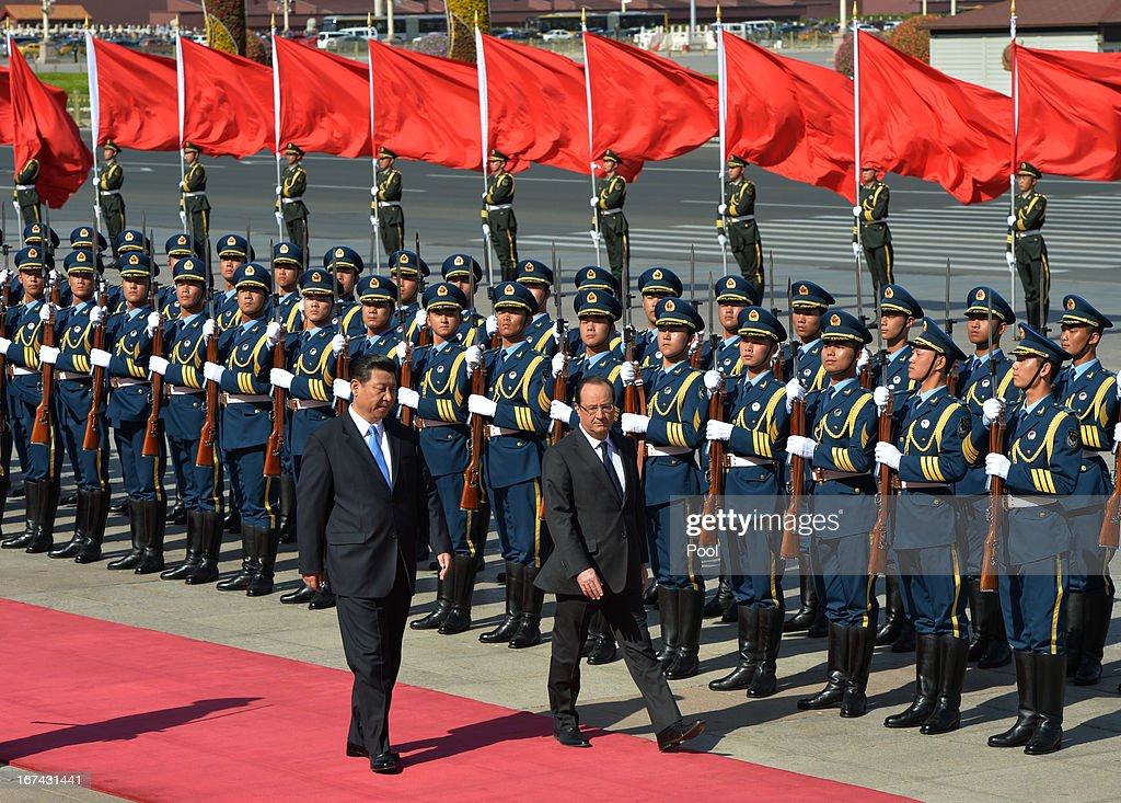 French President Francois Hollande (R) and Chinese President Xi Jinping inspect a guard of honor during a welcoming ceremony outside the Great Hall of the People on April 25, 2013 in Beijing, China. Hollande has begun a two day trade visit to China bringing with him a large French trade delegation.