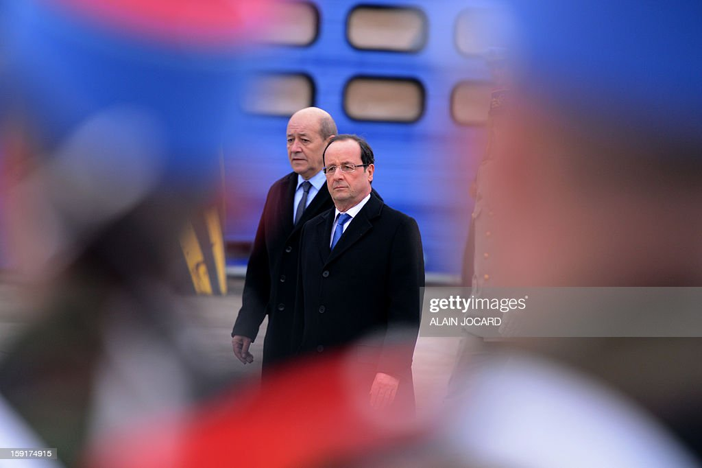French president Francois Hollande (C) and Defence minister Jean-Yves Le Drian (L) review troops on January 9, 2013 in Olivet, near Orleans, central France, as part of a visit to present his New Year's wishes to the French armed forces.