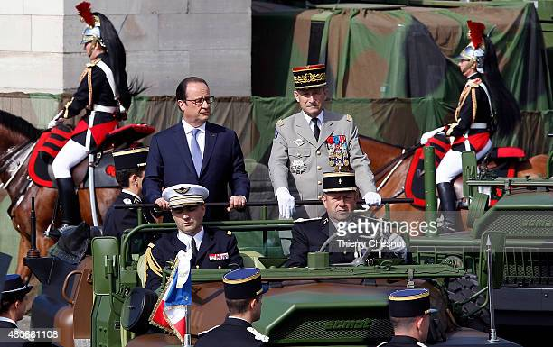 French President Francois Hollande and French Army ChiefofStaff General Pierre de Villiers stand in military vehicle during the annual Bastille Day...